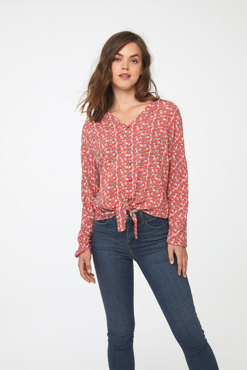 Woman wearing a silky, long sleeve, button front, v-neck red bird print blouse with self tie front and drop shoulder