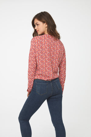 back of Woman wearing a silky, long sleeve, button front, v-neck red bird print blouse with self tie front and drop shoulder