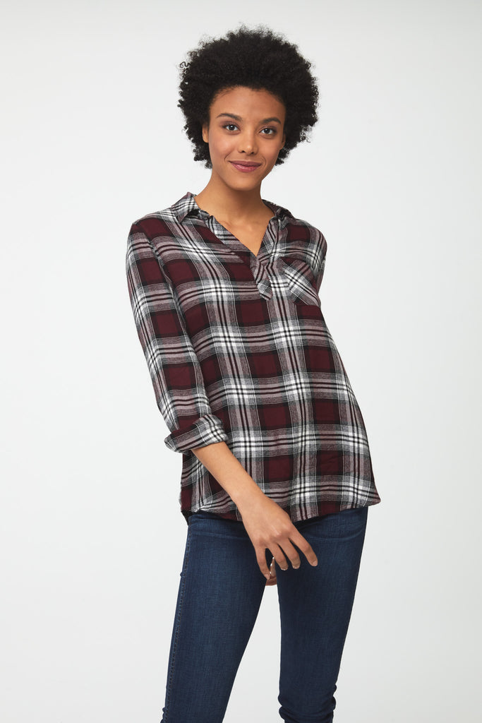 Woman wearing a relaxed, long sleeve V-neck burgundy plaid shirt with white accents and a single patch chest pocket
