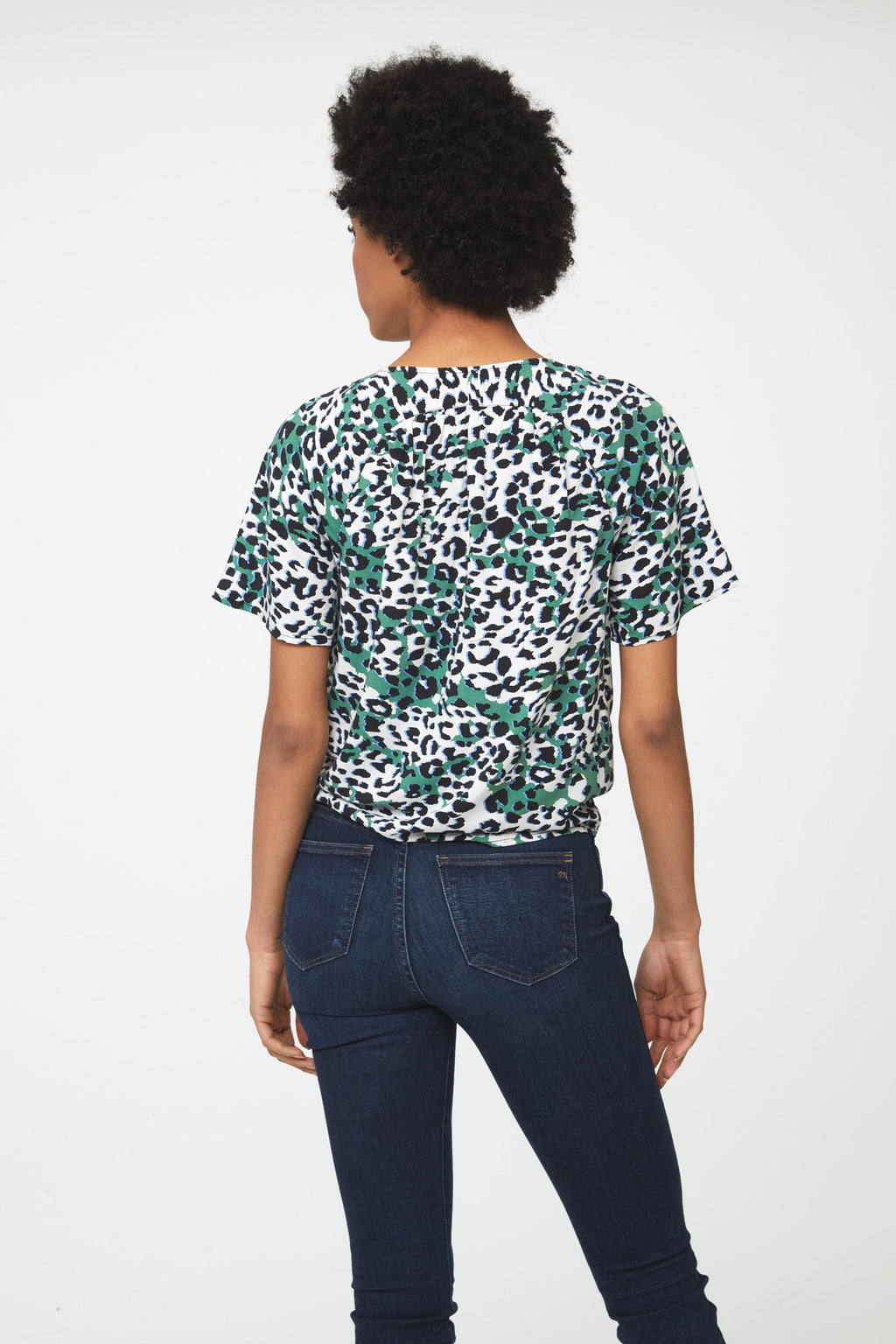 back of woman wearing a silky, short sleeve, button front v-neck blouse in green, white, and black leopard print with self tie front