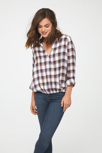 Woman wearing a white and brown plaid, Long Sleeve Collared V-Neck Shirt with Wrap Silhouette and Elastic Bottom Hem