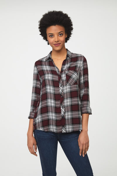 Woman wearing a long sleeve, button-down plaid shirt in deep maroon red and white with a single chest pocket