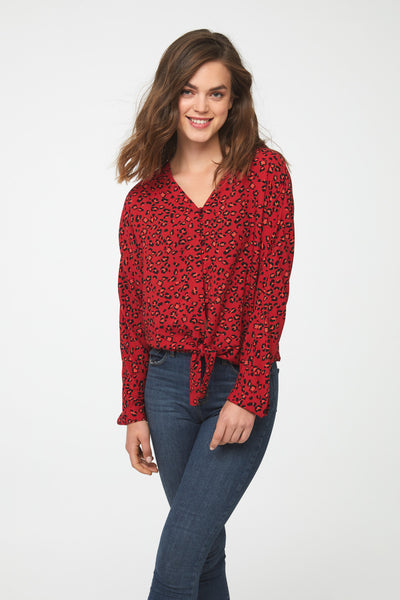 Woman wearing a silky long sleeve, button front, v-neck blouse in red and black leopard print with self tie front