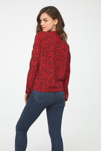 back view of woman wearing a silky long sleeve, button front, v-neck blouse in red and black leopard print with self tie front