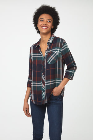 Woman wearing a long sleeve, button-down plaid shirt in deep blue, green and brown with white accents and a single chest pocket