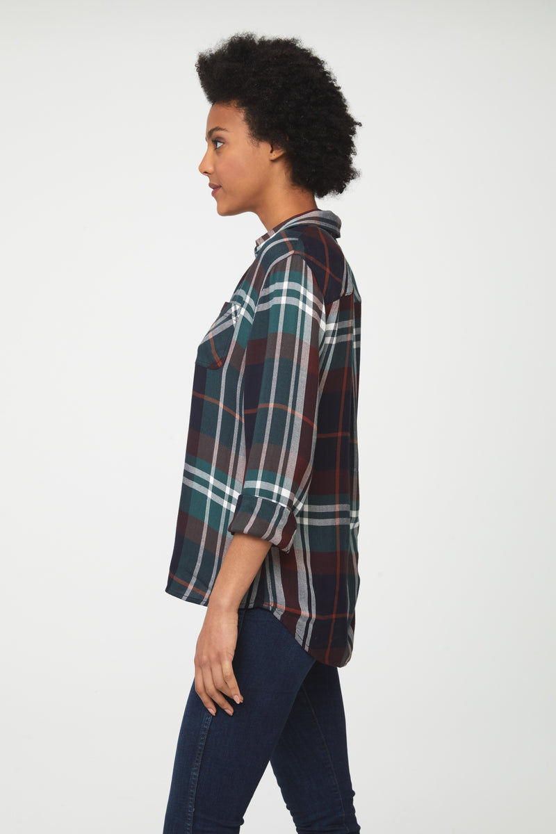 Side view of woman wearing a long sleeve, button-down plaid shirt in deep blue, green and brown with white accents and drop back hem