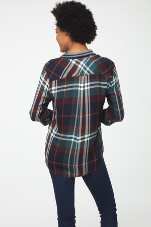 Back view of woman wearing a long sleeve, button-down plaid shirt in deep blue, green and brown with white accents and drop back hem