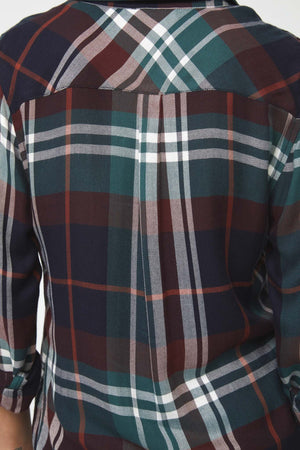 close view of long sleeve, plaid shirt in deep blue, green and brown with white accents