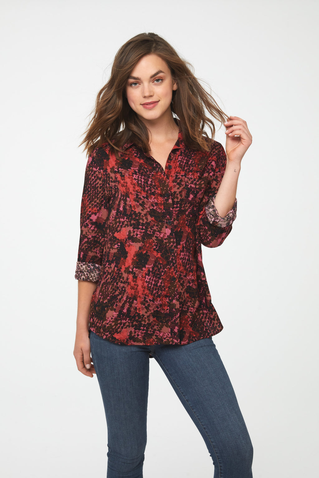 Woman wearing a classic, long sleeve button down, collared shirt  in red snakeskin print with single chest pocket and drop hem back