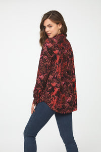 back view of Woman wearing a classic, long sleeve button down, collared shirt  in red snakeskin print with single chest pocket and drop hem back