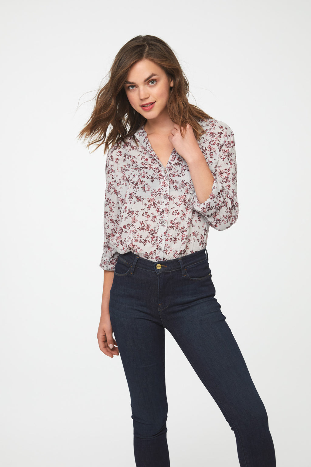 woman wearing a white, long sleeve, button-down blouse in vintage-floral print with a single chest pocket and drop back hem