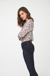 side view of woman wearing a white, long sleeve, button-down blouse in vintage-floral print with a single chest pocket and drop back hem