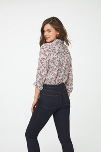 back view of woman wearing a white, long sleeve, button-down blouse in vintage-floral print with a single chest pocket and drop back hem