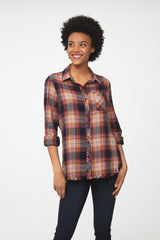 Woman wearing long sleeve button front flannel shirt in orange and brown plaid and frayed detailing