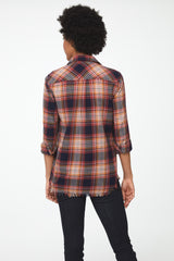 back view of Woman wearing long sleeve button front flannel shirt in orange and brown plaid and frayed detailing