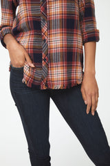 Woman wearing a orange and brown flannel shirt with frayed hem detailing