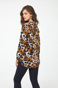 back view of woman wearing a long sleeve button-down blouse in camo-floral print with a single chest pocket and drop back hem