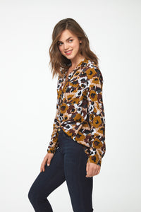 Side view of woman wearing a long sleeve button-down blouse in camo-floral print with a single chest pocket and drop back hem