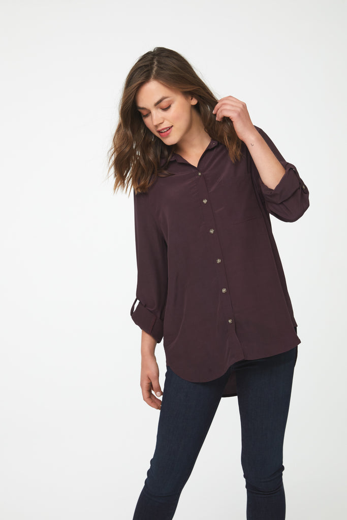 woman wearing brown, button-down shirt with drop back hem and cuffed sleeves