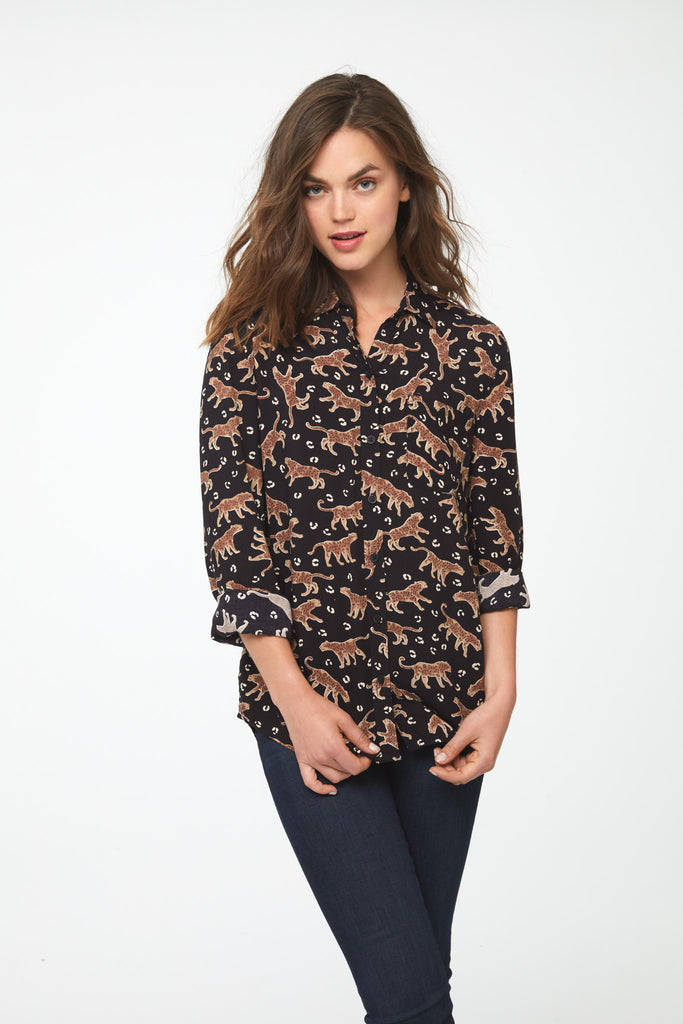 woman wearing a black, long sleeve button-down blouse with leopards, single chest pocket and drop back hem