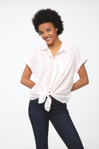 Woman wearing a cotton, tie-front, button-down short sleeve, boxy fit shirt with pink and white stripes