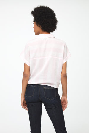 back of woman wearing a cotton, tie-front, button-down short sleeve, boxy fit shirt with pink and white stripes