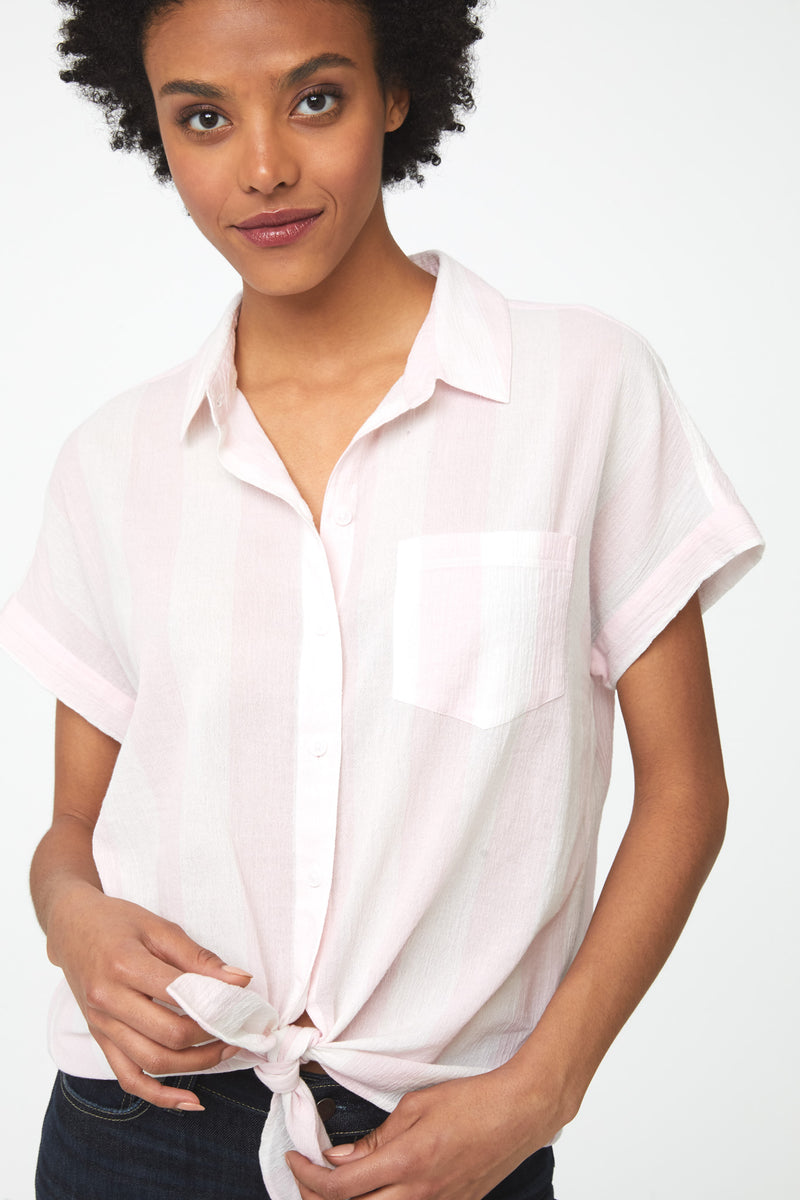 close up of Woman wearing a cotton, tie-front, button-down short sleeve, boxy fit shirt with pink and white stripes