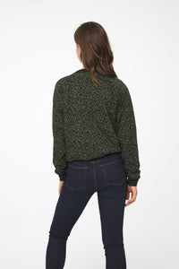 Back view of woman wearing a green and black leopard print, lightweight bomber jacket with black ribbed hem