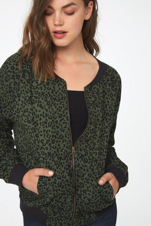 Close view of woman wearing a green and black leopard print, lightweight bomber jacket with black ribbed hem