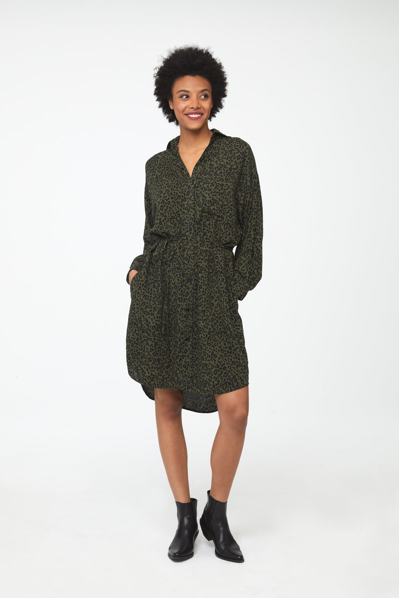 Woman wearing green leopard print, long sleeve, collared, button-front shirt dress with self-belt