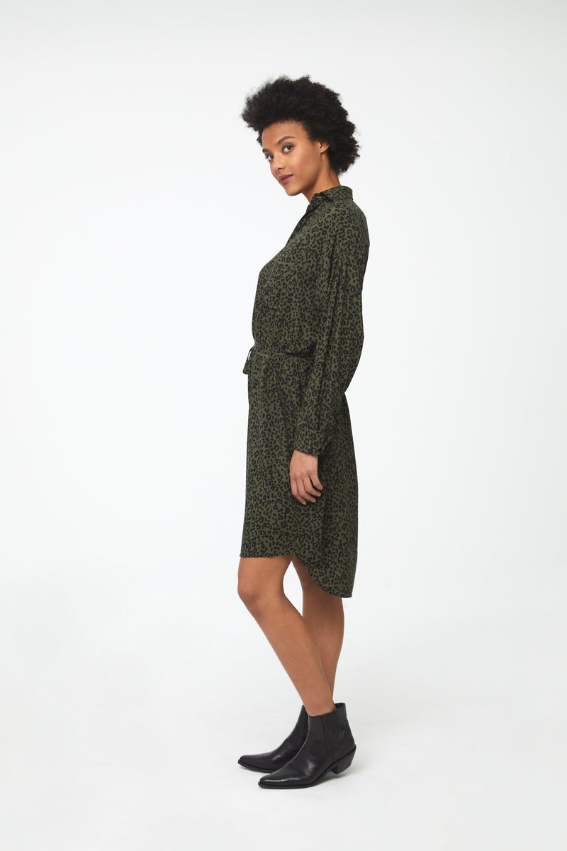 Side view woman wearing green leopard print, long sleeve, collared, button-front shirt dress with self-belt