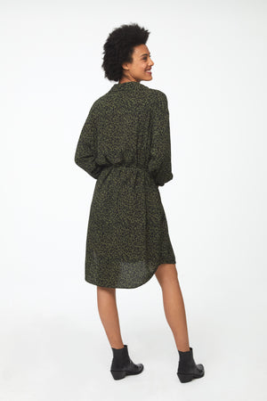 Side view of Woman wearing green leopard print, long sleeve, collared, button-front shirt dress with self-belt