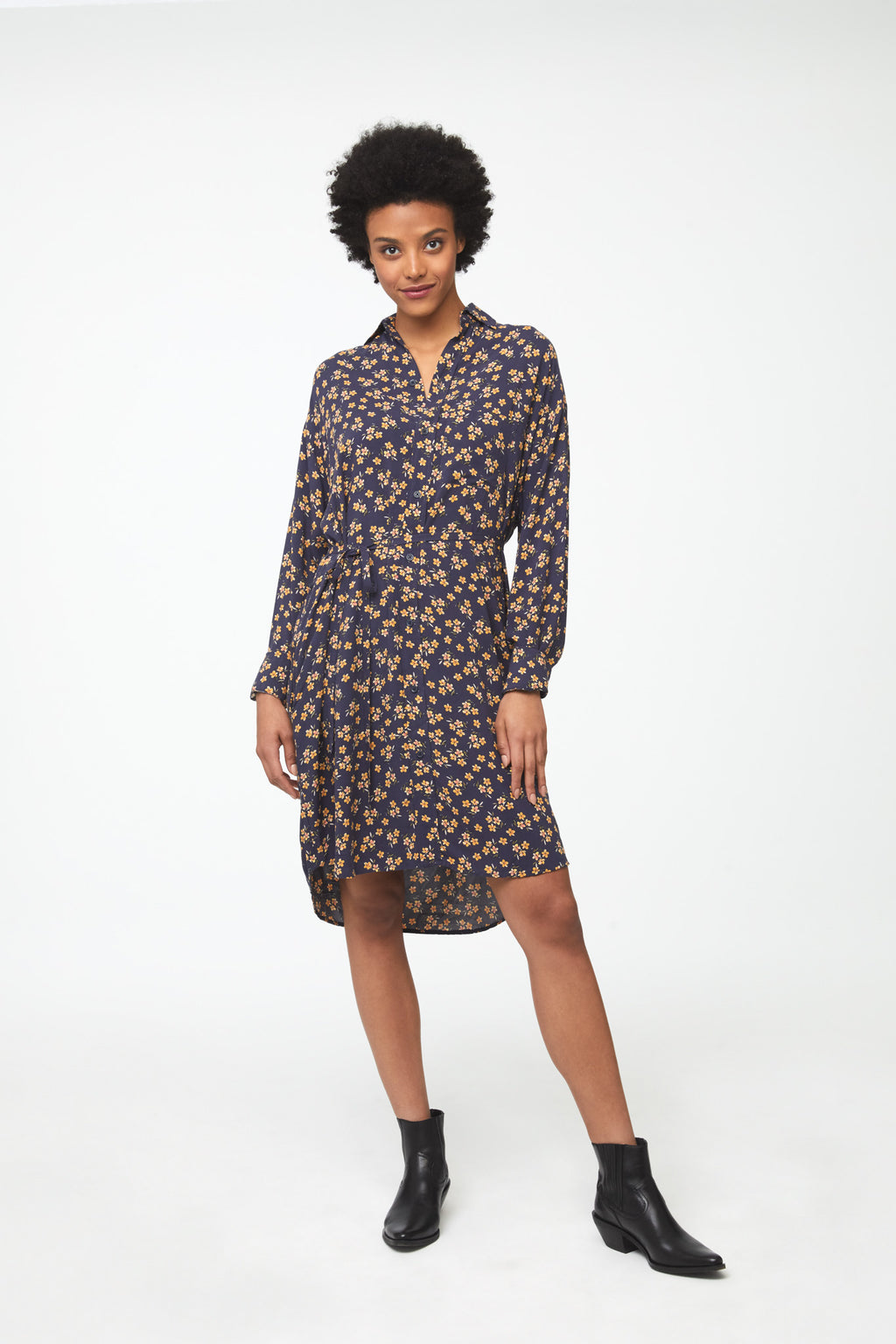 Woman wearing navy floral print, long sleeve, collared, button-front shirt dress with self-belt