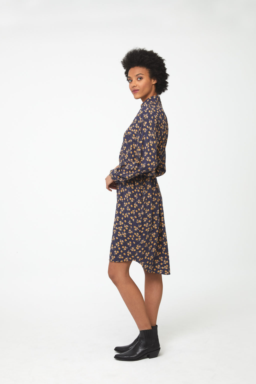 Side view woman wearing navy floral print, long sleeve, collared, button-front shirt dress with self-belt
