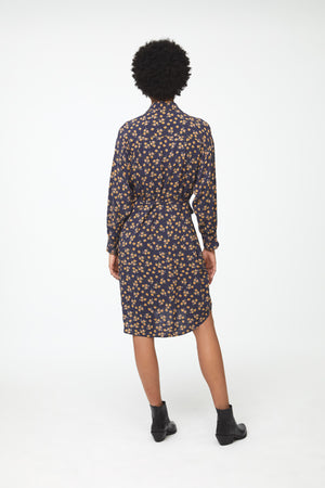 Back view woman wearing navy floral print, long sleeve, collared, button-front shirt dress with self-belt