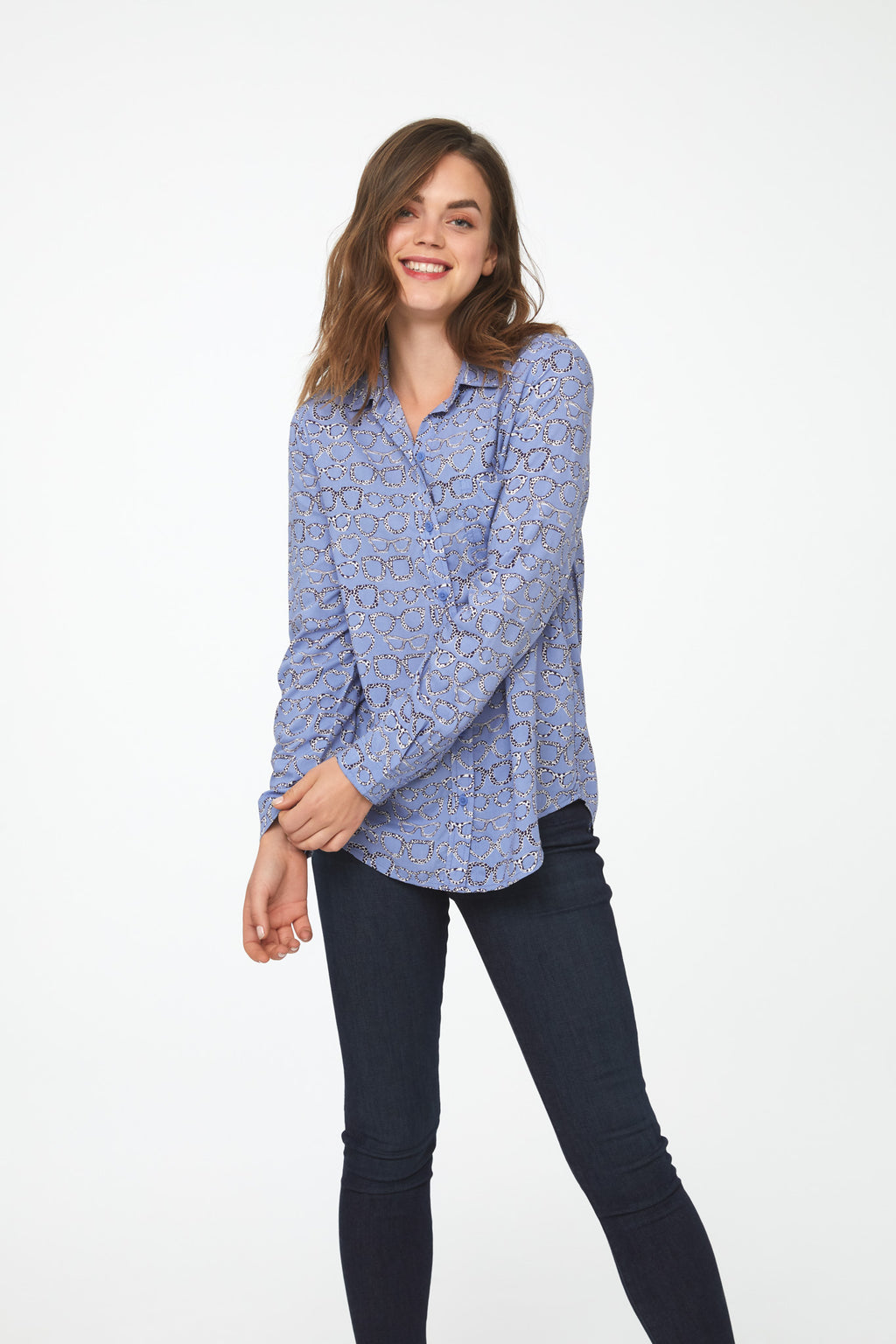 woman wearing a periwinkle, long sleeve button-down blouse with eyeglass print, single chest pocket and drop back hem