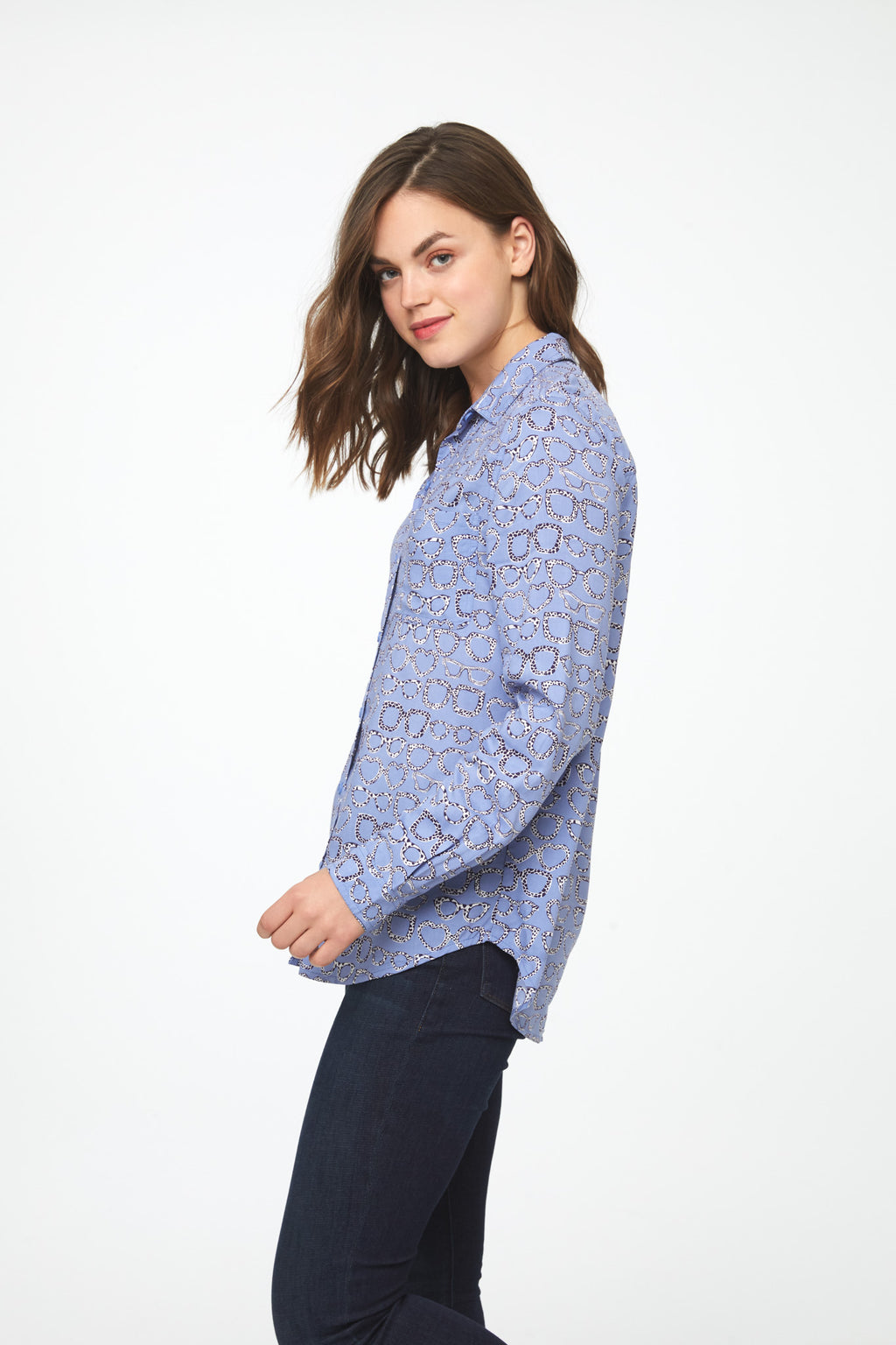 side view of woman wearing a periwinkle, long sleeve button-down blouse with eyeglass print, single chest pocket and drop back hem