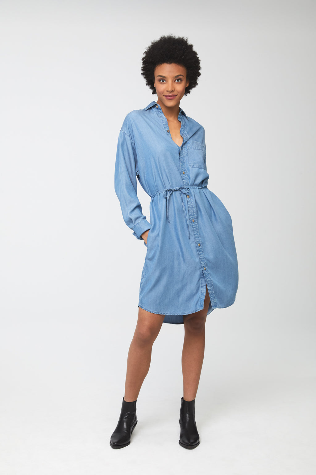 Woman wearing light-blue tencel denim, long sleeve, collared, button-front shirt dress with self-belt