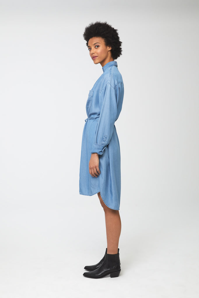 Side view woman wearing light-blue tencel denim, long sleeve, collared, button-front shirt dress with self-belt