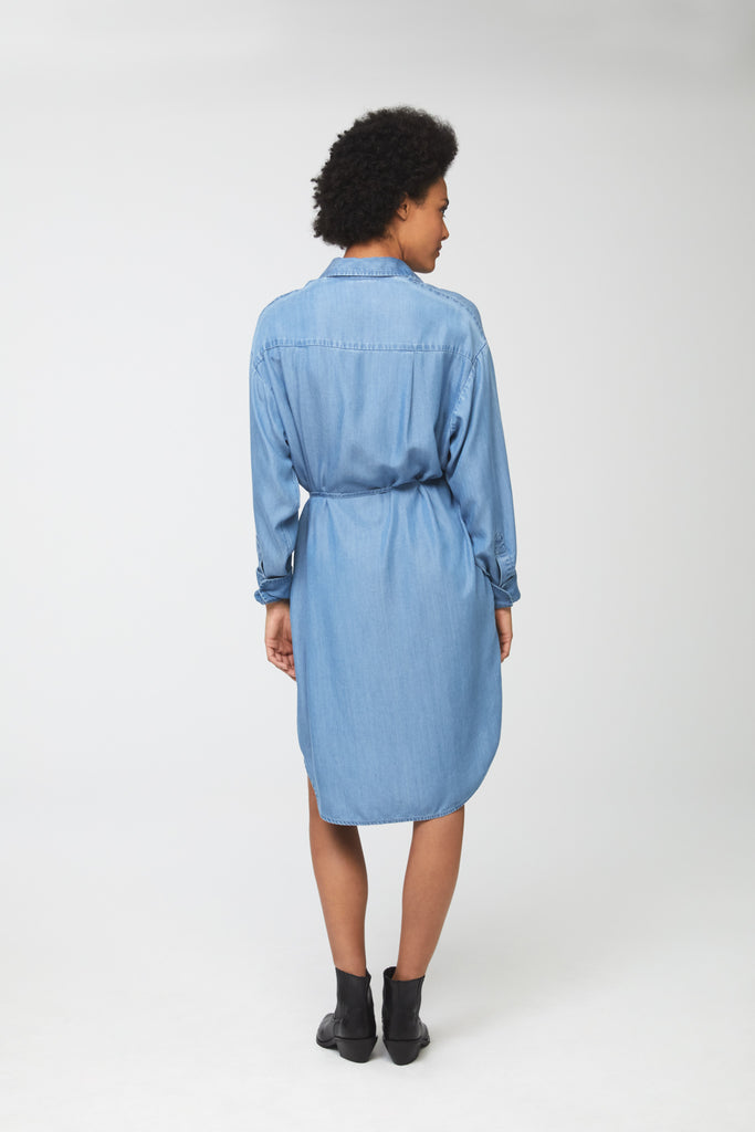 Back view woman wearing light-blue tencel denim, long sleeve, collared, button-front shirt dress with self-belt
