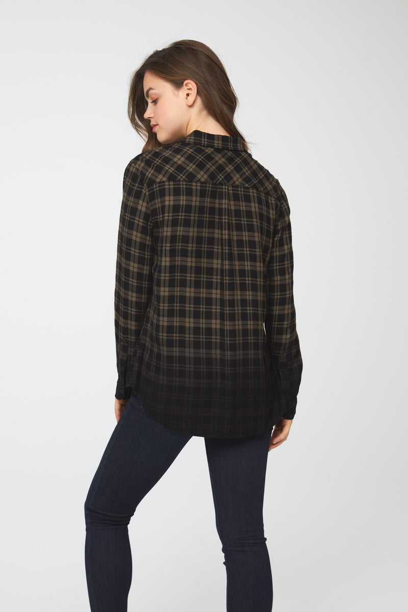 Back of woman wearing a green plaid button-down shirt with dip-dyed black hem and cuffs
