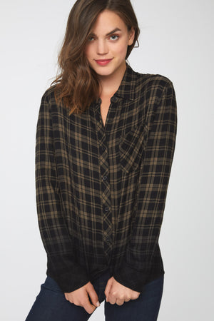 Woman wearing a green plaid button-down shirt with dip-dyed black hem and cuffs