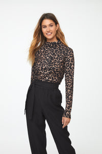 front view of Woman wearing a long sleeve leopard-print mockneck sweater