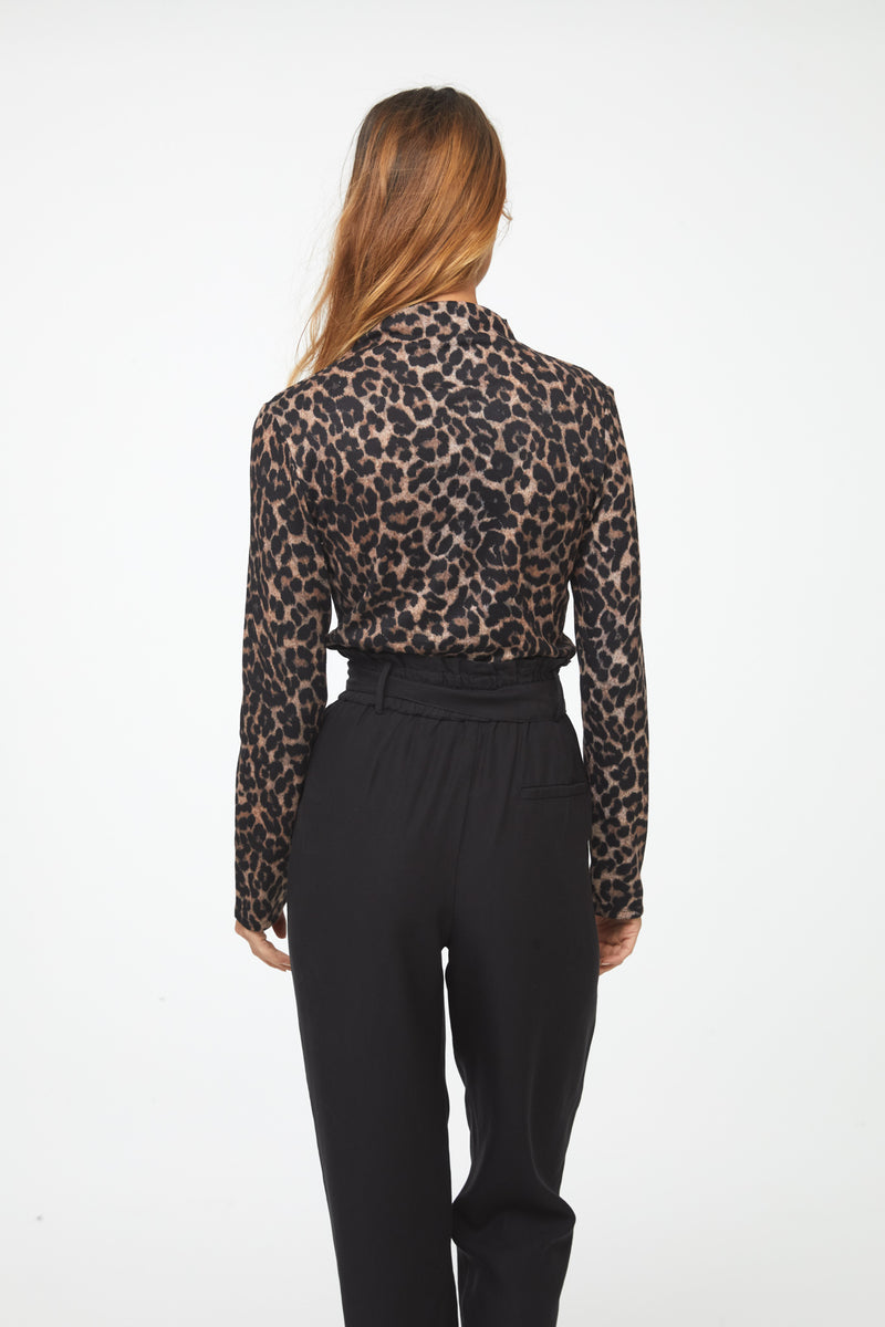 Back of woman wearing a long sleeve leopard-print mockneck sweater