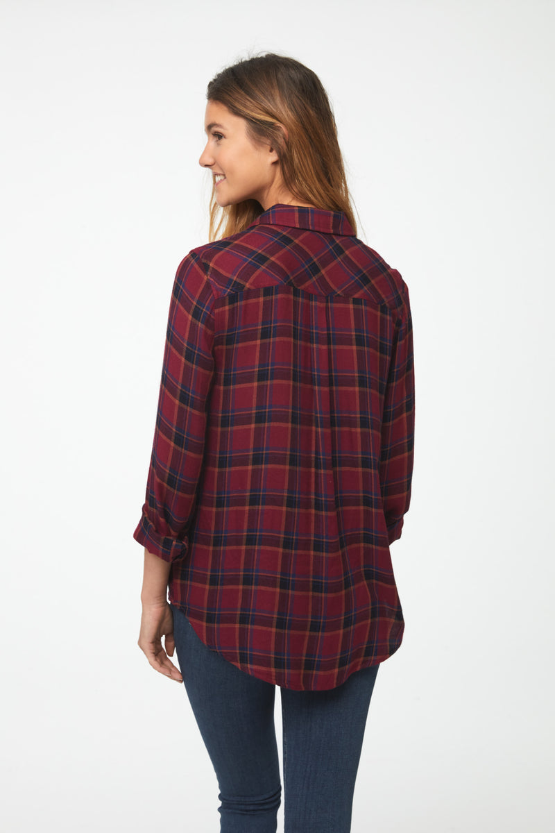 back view of woman wearing a long sleeve, button-down, crimson red plaid shirt with single chest pocket