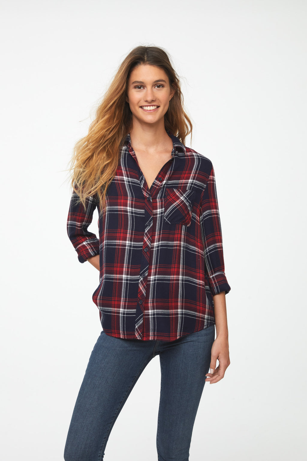 Woman wearing a long sleeve, button-down plaid shirt in red, white, and blue tri-color with a single chest pocket