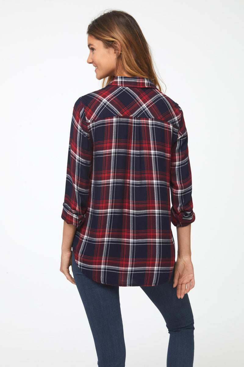 Back view of woman wearing a long sleeve, button-down plaid shirt in red, white, and blue tri-color with a single chest pocket and drop back hem