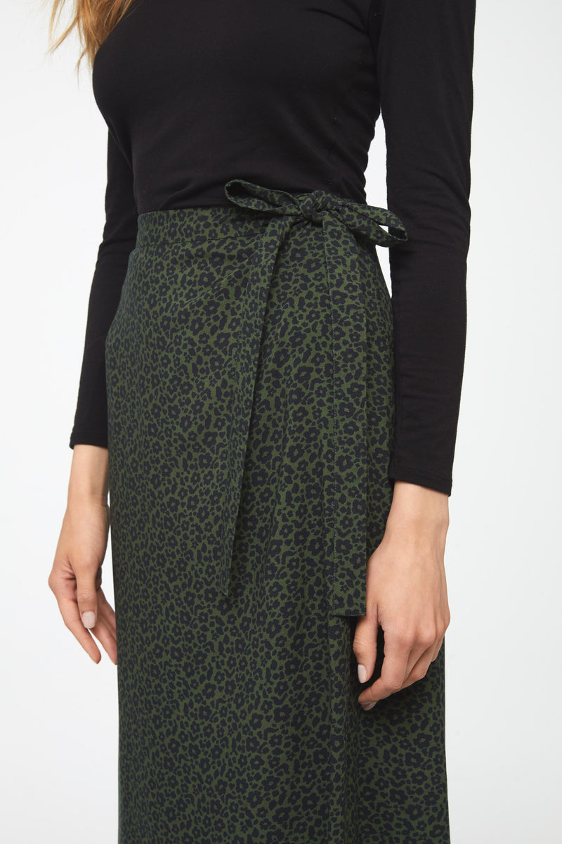 woman wearing midi length, side tie, wrap skirt in forest green and black floral print