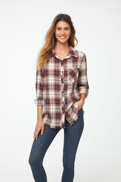 Woman wearing long sleeve, button front flannel shirt in red, yellow, and blue plaid with frayed hem detailing