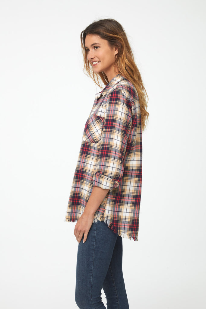Side view Woman wearing long sleeve, button front flannel shirt in red, yellow, and blue plaid with frayed hem detailing